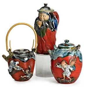 Sumida gawa pottery three pots with figures in relief on red ground early 20th c chocolate pot with figural head teapot with figures in relief and covered pot with pouring spout all marked tall