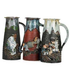 Sumida gawa pottery three pitchers with figures on rock formations in relief on black or deep red ground early 20th c mark for ryosai tallest 12 14