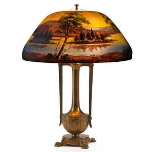 Moe bridges table lamp its shade reversepainted with lake scene at dusk on an aesthetic movement style bronze base 1920s chipped glass bronze patinated metal two sockets shade signed 23 x 1