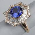 Tanzanite and diamond dinner ring ca 1980 faceted circular cut tanzanite 40 cts by formula within a radial frame of tapered baguette cut diamonds and scalloped surround of circular brilliant cut