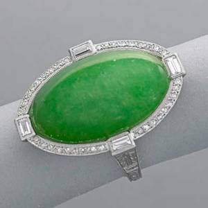 Art deco platinum jade and diamond ring oval jade cabochon 22 x 14 x 6 mm framed by a line of small circular cut and four baguette cut diamonds elaborate scroll pierced gallery and shank with incis