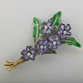 Enameled gold diamond bouquet brooch ca 1895 rose cut diamonds in silver veins on translucent enamel leaves support five purple shaded violets with omc diamond centers oval tag mark for tiffany