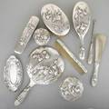 Japanese export silver vanity set ca 1900 ten pieces with embossed iris motifs on stippled ground two round covered boxes 4 x 3 pin tray 6 button hooks shoe horn 8 34 three brushes lo