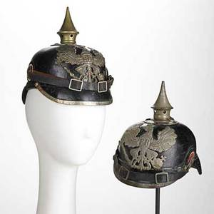 Two german pickelhaube both in leather one with brass mountings the other with tin brass mounted marked kbag 1915 on brim each 8 12 x 6 x 9