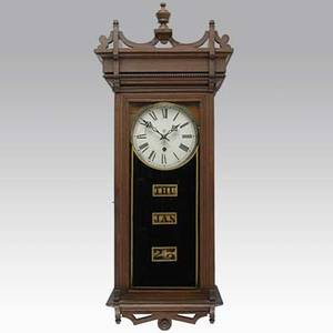Waterbury calendar wall clock keating model with walnut case and time and strike movement late 19th c 37 x 15 58 x 9 14