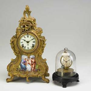 Ansonia mantle clock gilt metal in the french style with porcelain panel and time and strike movement late 19th c together with novelty globe clock under glass dome patent date 1856 ansonia 14