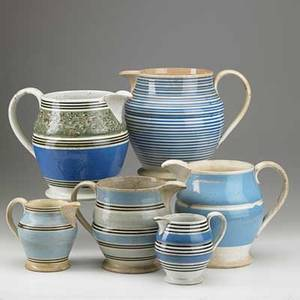 English mocha pitchers six 19th c three with striped decoration one with blue panels one with blue panel and splotch decoration and one with narrow vertical stripes largest 8