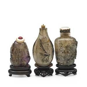 Chinese rock crystal snuff bottles three with relief decoration and bases 19th c tallest 3 34 with base
