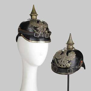 German pickelhaube two in leather one with brass mountings the other tin early 20th c brass mounted marked kbag 1915 on brim each 8 12 x 6 x 9
