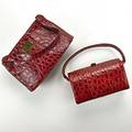 Two red alligator purses square tapered with vacant goldplated panel zipper top black file interior 10 x 5 78 barrelshaped with gilt hardware hinged closure red leather interior 8 x 4 1