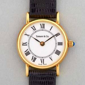 Tiffany  co 14k gold ladies watch 1991 white face with roman hours sapphire crown 29 mm swiss original black lizard strap presentational inscription on back of case