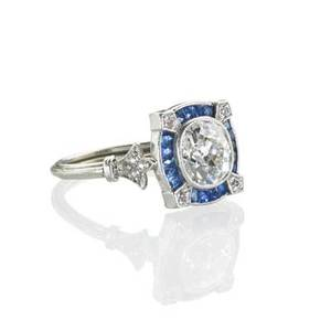 Art deco diamond and sapphire platinum ring oval cushion cut diamond approx 89 ct centers conforming quartered sapphire channel trefoil diamond shoulders and reeded hoop size 5 12 25 dwt p