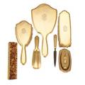 Tiffany  co 18k gold vanity set eight pieces ogee edge raised oval cartouches with interlaced monograms hand mirror 10 34 hair brush 8 1516 garment brush 7 nail buffer on 7 tray sol