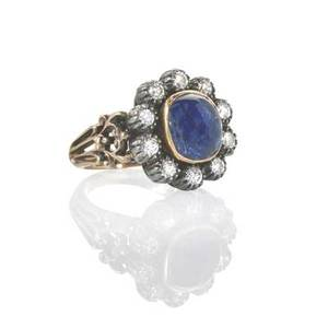 French sapphire and diamond ring cabochon cut blue sapphire approx 370 cts framed by ten brilliant cut diamonds approx 70 ct in silver cut collets scroll pierced hoop mid 20th c french m