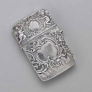Baroque 800 silver card case cushion shaped raised with foliate scroll and putti hinged with thumb press deployment ca 1900 monogram on reverse austrian and french import marks 3 34 x 2 38