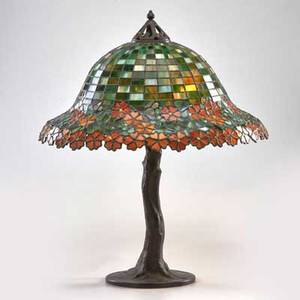 Handel table lamp base in the form of a tree trunk meriden ct early 20th c married to reproduction foliate shade in shades of orange green and yellow patinated metal leaded glass three sock