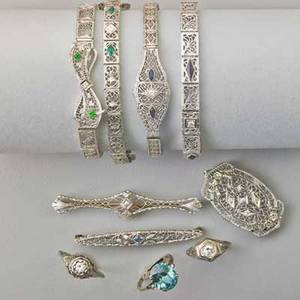 Art deco white gold filigree jewelry with diamonds 14k gold bracelet with diamond and emerald accented bow 14k gold diamond sapphire strap bracelet two 10k gold bracelets diamond panel straps with