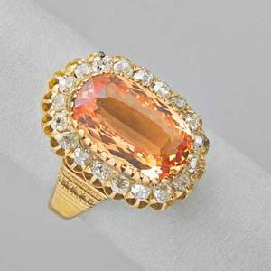 Imperial topaz and diamond 15k gold ring oval faceted topaz 6 cts by formula framed by a line of omc diamonds 1 cts tw embossed shoulders ca 1900 size 7 6 dwt