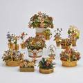Jane hutchenson etc enameled floral arrangements two fleurs des siecles in silver gilt with pots by gorham one silver gilt watering can retailed by cartier three gilt metal baskets with winter o