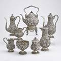 Eight piece sterling repousse coffee service bulbous or pearshaped vessels profusely decorated with deeply chased fruit and floral decorations floral finials kettle on branchfooted stand 15 th