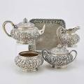 Peter l krider repousse silver tea service four piece chased with dense blossoms and tobacco leaves teapot creamer sugar and waste bowl monogrammed under base and dated 1886 801 cushionshape
