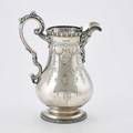 Tiffany  co sterling water pitcher pearshaped with incised floral garlands leafy spout and serpentine handle gadroon rim egg and dart applied ribbon foot grosjean and woodward 1859 inscribed