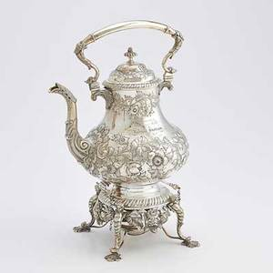 Jones ball and poor coin silver kettle on stand pearshaped body chased with flowers and foliage scroll and acanthus spot and handle gadrooned stand with flowers and cherubs ivory insulators bost