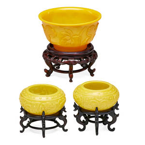 Chinese peking glass bowls three one small center bowl with floral relief carved design and one pair of finger bowls with carved dragon foliate design each with hardwood stand 20th c tallest 4 1