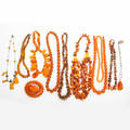 Collection of amber jewelry twelve pieces includes butterscotch raw natural and pressed five strands of round or oblate beads four strands of pebble beads butterscotch cabochon brooch 2 x 1 1