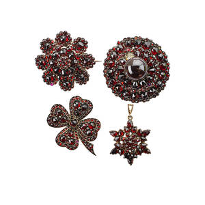Collection of victorian bohemian garnet jewelry four pieces three brooches and a pendant in circular star burst floral and fourleaf clover forms gilt metal ca 18901900 unmarked largest 1 1
