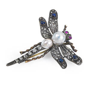 Jeweled dragonfly brooch naturalistically rendered in silver topped 14k gold wings and abdomen set with rose cut diamonds sapphire cabochons ruby eyes two pearls form thorax 93 x 96 mm and 6