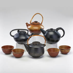 Asian eight ceramic pieces three teapots in black glaze and one in red with four matching cups late 20th c all marked largest 5 12 x 9