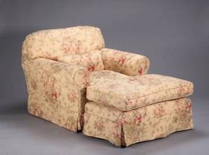 A UPHOLSTERED CLUB CHAIR WITH MATCHING OTTOMAN