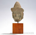 Carved Stone Head of a Deity Khmer Angkor periodstyle wearing a flared headdress with a coneshaped brim decorated with geometric