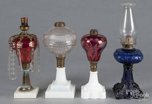 Four assorted glass fluid lamps