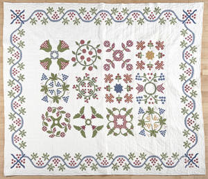 Contemporary cross stitch sampler quilt with a trailing vine border