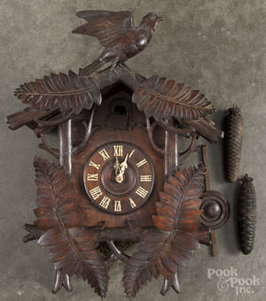 Black Forest carved cuckoo clock with a bird crest