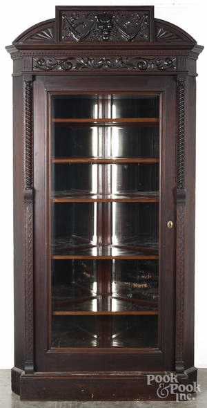 Victorian mahogany corner cupboard with a carved crest and mirrored back
