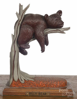 Contemporary carved bear on a tree limb