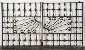 Pair of decorative cast iron window grates with a central sun motif