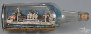 Folk art painted model ship and village in a bottle