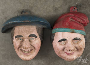 Two painted cast iron wall masks
