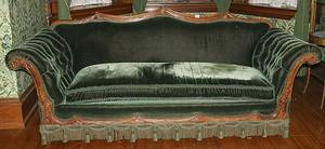 Green upholstered sofa with swag carving