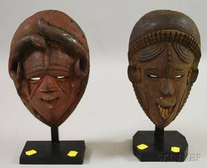 Two IgboIgbostyle Carved Wooden African Masks on Stands