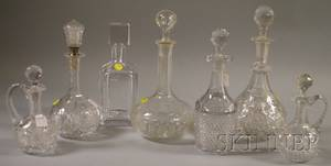Four Colorless Cut Glass Decanters Two Cruets and a Kosta Boda Crystal Decanter