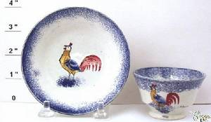 Blue spatter miniature cup and saucer with yellow blue and red rooster