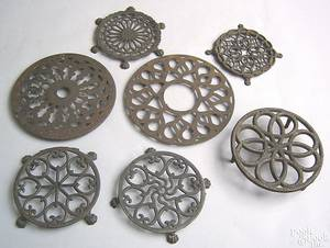 Seven round reticulated cast iron trivets 19th c