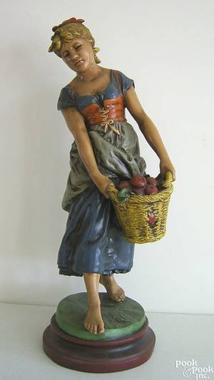 Cast white metal figure of a young woman carrying a basket of apples earlymid 20th c